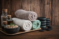 Spa concept. Towels with sea salt, massage oil in vintage bottle and stones for stone massage on wooden background Stock Images
