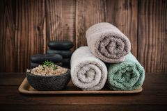Spa concept. Towels with sea salt  and stones for stone massage on wooden background Stock Image