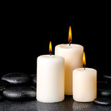 Spa concept of white candles on zen basalt stones with drops, cl Royalty Free Stock Photography