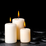 Spa concept of white candles on zen basalt stones with drops, Royalty Free Stock Images