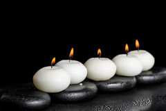 Spa concept of white candles on zen stones with water dew black Stock Photo