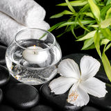 Spa concept of white hibiscus flower, bamboo, round vase and tow Stock Photo