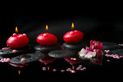 Spa concept of white and red orchid (cambria), three red candles. Spa concept of white and red orchid (cambria), three  red candles and pearl beads on zen stones Stock Photos