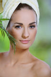 Spa concept. Young beautiful woman touching face green plants Stock Photos