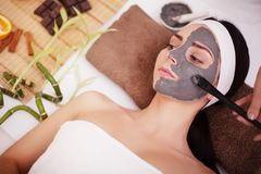 Spa concept. Young woman with nutrient facial mask in beauty salon, close up Stock Image