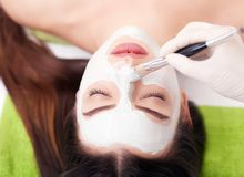 Spa concept. Young woman with nutrient facial mask in beauty salon, close up.  Royalty Free Stock Photos