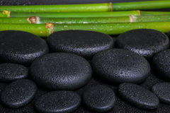 Spa concept of zen basalt stones and bamboo with dew,. Closeup stock photography