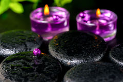 Spa concept of zen basalt stones with bead, drops, lilac candles Stock Photo