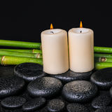 Spa concept of zen basalt stones, candles and natural bamboo. With dew, closeup royalty free stock photo