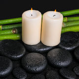 Spa concept of zen basalt stones, candles and natural bamboo wi. Th dew, closeup royalty free stock images