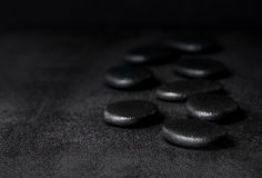Spa concept of zen basalt stones with water drops on black backg. Round, closeup Stock Photography