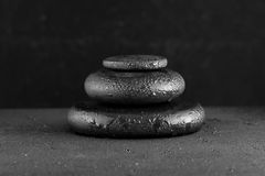 Spa concept of zen basalt stones with water drops on black Royalty Free Stock Photos