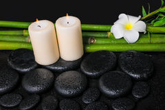 Spa concept of zen basalt stones, white flower frangipani, candles and natural bamboo with dew, closeup stock photography
