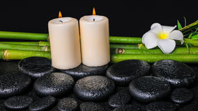 Spa concept of zen basalt stones, white flower plumeria, candles Stock Photos
