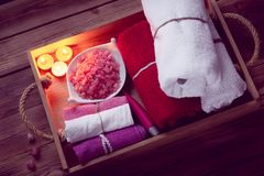 Set of bathhouse accessories for SPA in Low-key lighting. SPA consist from colorful towels, pink sea salt and candles on a wooden tray. Picture in Low-key stock image