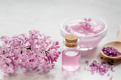 Spa cosmetic set with lilac flowers stone desk background Royalty Free Stock Photo