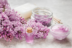 Spa cosmetic set with lilac flowers stone desk background Stock Photo