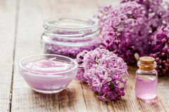 Spa cosmetic set with lilac flowers wooden desk background. Spa cosmetic set with lilac flowers on wooden desk background Royalty Free Stock Photography