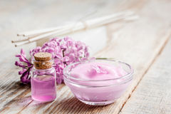 Spa cosmetic set with lilac flowers wooden desk background Stock Photo