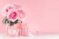 Spa cosmetics products, roses in pastel pink and silver color - cream, bath salt, essential oil, soap, bottle, bowl, towel.