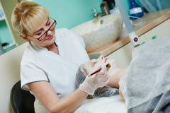 Spa cosmetologist applying facial mask Stock Photos