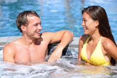 Spa couple happy in wellness hot tub jacuzzi. Laughing having fun being in love. Happy young lovers on honeymoon vacation travel to luxury resort spa retreat stock photos