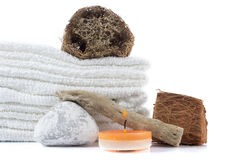 Spa decoration with stones, wooden items, candle and white towel Stock Photos