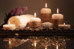 Free Spa Decorative Set With Sea Pebbles, Salt, Aromatic Candles, Towel And Flower. Golden Composition In Low Key, Dark Photo Royalty Free Stock Image - 152858216