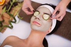 Spa Den härliga unga kvinnan får ansikts- leramaskering på brunnsorten, l Arkivfoto