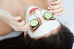 Spa El cosmetólogo aplica la máscara a la cara de jóvenes hermosos Imagen de archivo