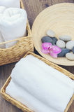 Spa elements. Orchid flower and towe with spa stones on wooden background stock images