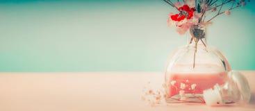 Spa eller wellnessbakgrund med rumdoftflaskan och blommor på pastellfärgad bakgrund, främre sikt Arkivfoton