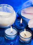 Spa essentials. Cream, candles with flower on blue background royalty free stock photo