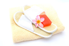 Spa essentials. Orange soap with beautiful pink Frangipani Plumeria flower and hygienic spa slippers on clean beige towel as beauty and wellness utensils. Image Royalty Free Stock Images