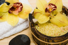 Spa essentials. (salt for bath, white towel and orchids Royalty Free Stock Image