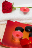 Spa essentials. (candle, stones and petals of red rose Royalty Free Stock Images