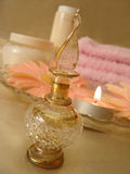 Spa essentials (beautiful bottle of perfume and candle, flowers,. Cream, towel on a background Stock Photo
