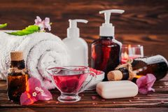 Spa essentials including natural oils, salt, soap and candle. Organic cosmetics concept. Spa essentials including natural oils, salt, soap and candle on wooden Royalty Free Stock Photo