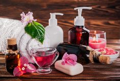 Spa essentials including natural oils, salt, soap and candle. Organic cosmetics concept. Spa essentials including natural oils, salt, soap and candle on wooden Stock Images