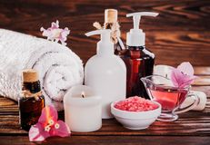 Spa essentials including natural oils, salt, soap and candle. Organic cosmetics concept. Spa essentials including natural oils, salt, soap and candle on wooden Stock Photography