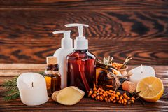 Spa essentials including sea buckthorn, lemon and ginger oils and candles. Organic cosmetics concept. Spa essentials including sea buckthorn, lemon and ginger Stock Photo
