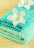 Spa essentials. Towels and flowers. Royalty Free Stock Photo