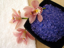 Spa essentials (violet salt, white towel and pink orchids) Stock Photos