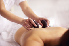 Spa experience hot stones back massage. Relaxing back massage with blurred background Royalty Free Stock Image