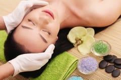 Spa Facial del cuidado La mujer joven de la belleza consigue un masaje principal en el salón Foto de archivo libre de regalías