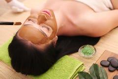 Spa Facial del cuidado Tratamiento de la cara La mujer en salón de belleza consigue a Marine Mask Imagenes de archivo