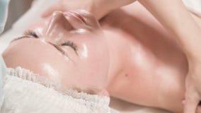 Spa facial Massage Yrkesmässig massageterapeut till flickor gör en uppmjukande ansiktsmassa till en attraktiv kund lager videofilmer