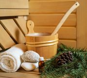 Spa, Finnish sauna and wellness setting with water bucket, oil essence, cones, Christmas tree branches, white towel on wooden royalty free stock photo