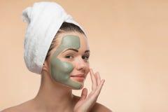 Spa flicka med en handduk på hennes head applicerande ansiktsbehandling Royaltyfri Bild