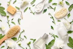 Spa floral background. Flat lay of various beauty care products decorated with simple white flowers, blank space for your text stock photography